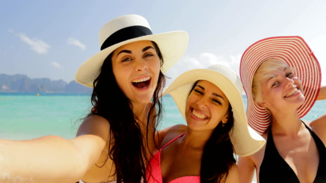 Girls On Beach Taking Selfie Photo On Cell Smart Phone, Cheerful Women In Bikini and Straw Hats On Summer Holiday video