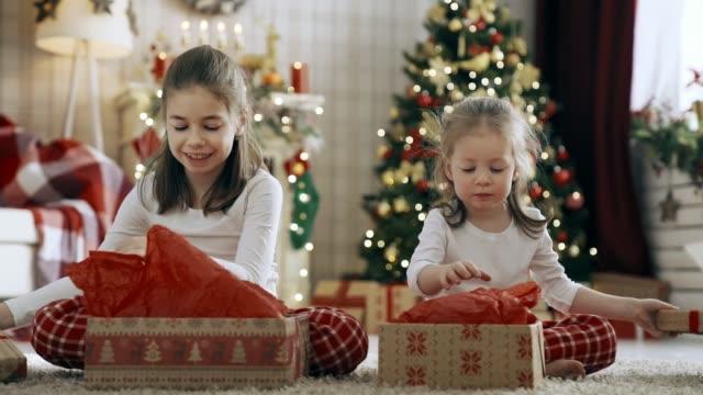 flickor öppna julklappar - christmas gift family bildbanksvideor och videomaterial från bakom kulisserna