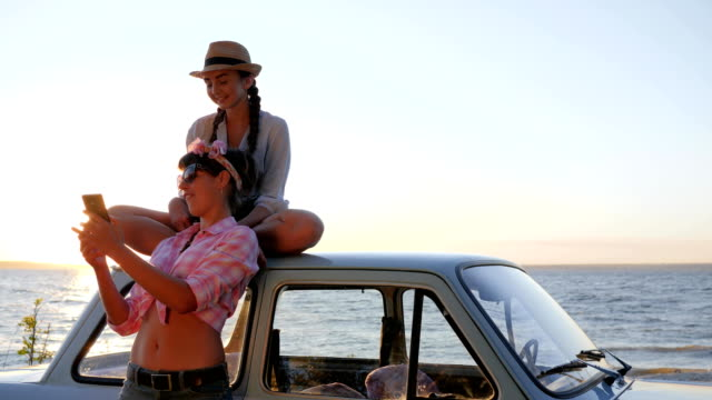 vídeos de stock, filmes e b-roll de foto de garotas no gadget perto de veículo na beira-mar, vídeo de registro namoradas a máquina na luz de fundo de céu - veículo terrestre