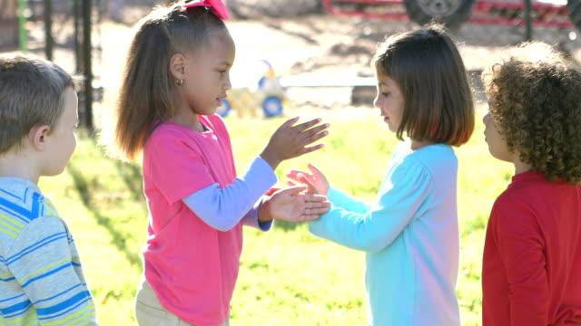 vidéos et rushes de regardez le jeu sur l'aire de jeux pour les filles, garçons - école primaire