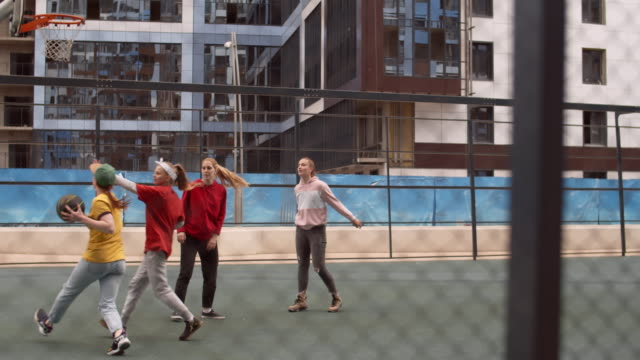 vídeos de stock e filmes b-roll de girls playing street basketball together - cercado