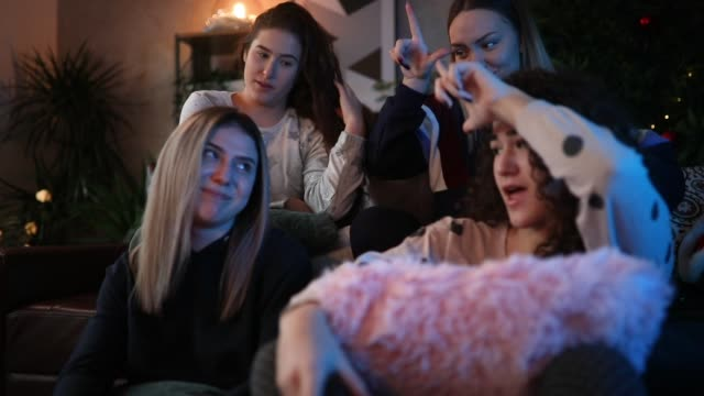 Girls playing video games and showing their friends loser sign