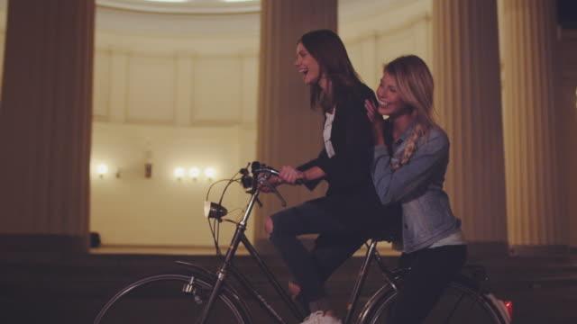 girls riding bike at night - friends стоковые видео и кадры b-roll