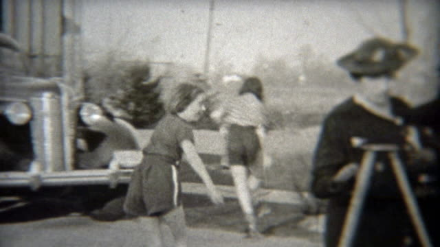 1937: Girls rollerskating on the sidewalks past their home. video