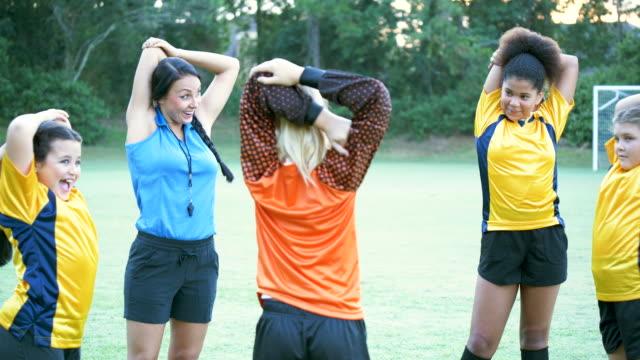 vídeos de stock e filmes b-roll de girls soccer coach leading team warm up - equipamento desportivo
