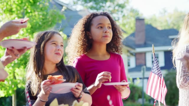 girls stand eating pizza with neighbours at a block party - vicino video stock e b–roll