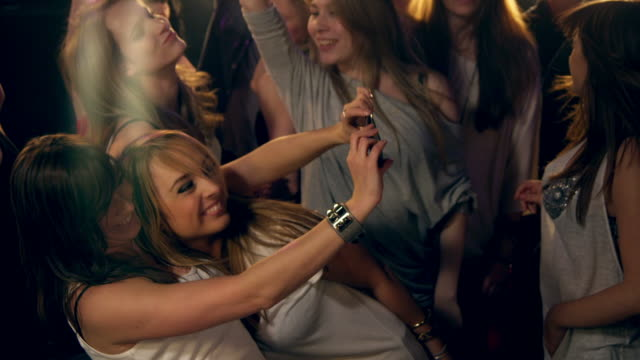Girls taking photos in disco video