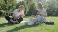 istock Girls teenage students sitting on green lawn in park with books, digital tablet, talking, laughing 1279283231