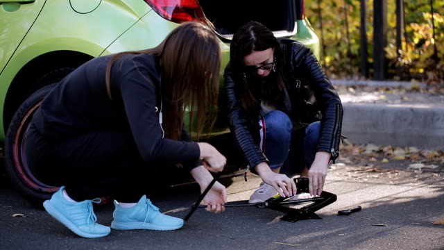Girls the side of the road learn to change the tyre on his car.