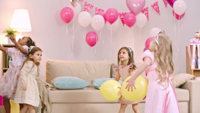 Girls Tossing Balloons in the Air Four playful little girls dressed like princesses tossing yellow balloons in the air at birthday party princess stock videos & royalty-free footage