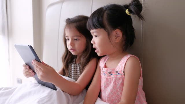Girls using digital tablet on The Bed video