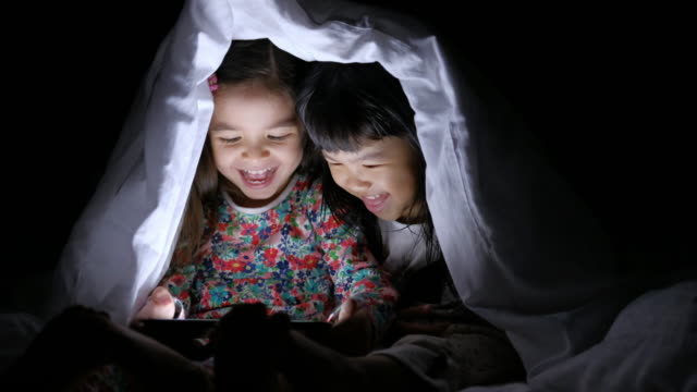 girls using tablet under blanket - video call with family video stock e b–roll