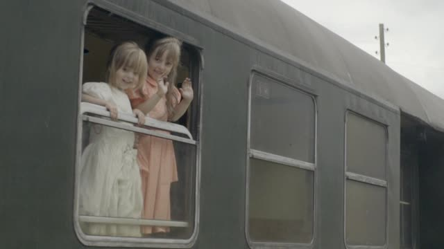 Girls waving from an old steam trains cabin