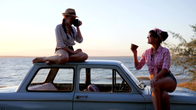 Girls with cups in Hands to vehicle on seafront in sundown, tea party of Friends to machine on coast sea in sunset video