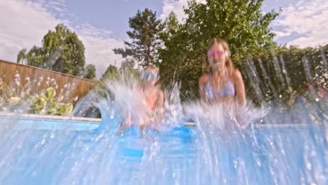 vídeos y material grabado en eventos de stock de niñas con la máscaras hacer señal con el pulgar de aprobación bajo el agua en la piscina - backyard pool