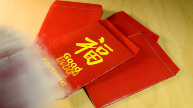Giving a red envelope or hong bao with yuan bills in Chinese New year video