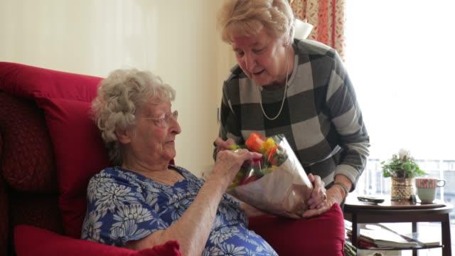 giving flowers to her elderly relative - serdeczny filmów i materiałów b-roll