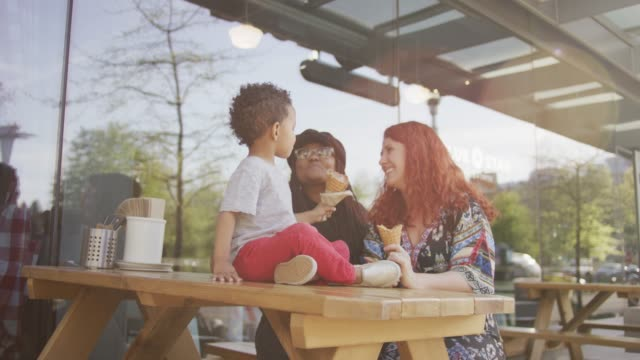 Giving Mom a Bite of Ice Cream A homosexual biracial female couple is sitting at a table outside with their son.  They all have ice cream cones and the son shares his with on of his moms. One woman is Caucasian and the other is African-American lesbian stock videos & royalty-free footage