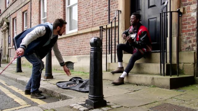 vídeos y material grabado en eventos de stock de dando a un músico callejero - compartir