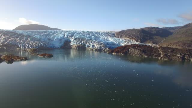 aerial glacier dominates landscape in calm fjords reflecting water - fiordo video stock e b–roll
