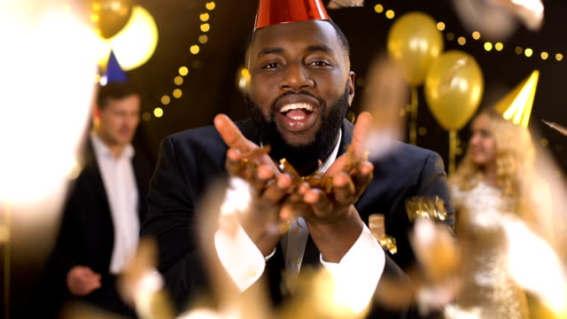Glad african male blowing gold confetti dancing night club, holiday celebration