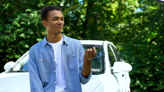Glad teenage male with car keys getting in car admiring new automobile, driving Glad teenage male with car keys getting in car admiring new automobile, driving car dealership stock videos & royalty-free footage