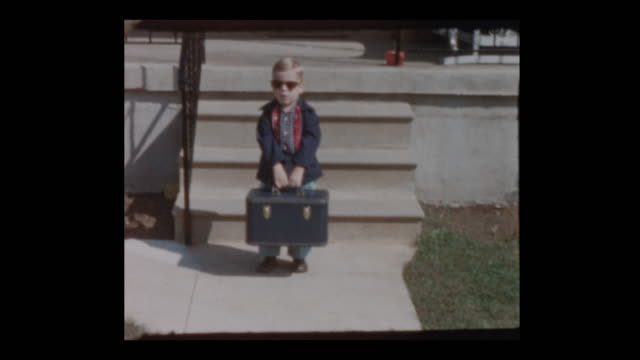 Glam 50's Mom and boy in sunglasses carries old fashioned vintage suitcase