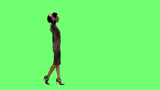 Glamour femelle Brunette dans une robe moulante avec élégance marchant sur un vert de maquette d'écran en arrière-plan. - Vidéo