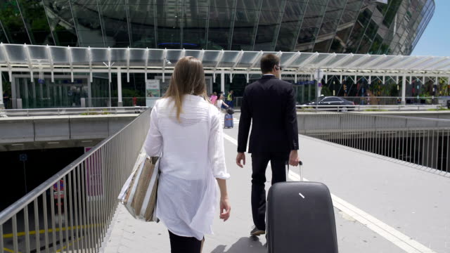 Glamorous female and bodyguard with her luggage walking at the airport, tourism video