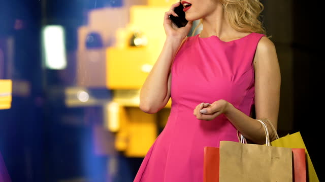 Glamorous girl enjoying expensive shopping, talking over phone, fashion boutique video