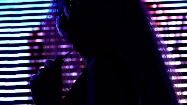 Glamorous model in sunglasses with lollipop under disco club illumination, style