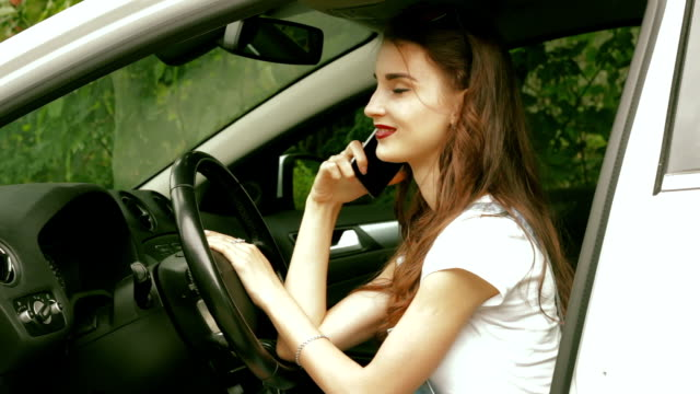 glamour lady sitting in the car while driving and talking on the phone video