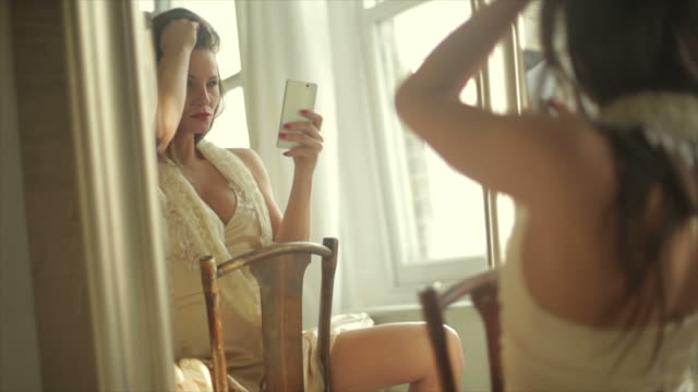 Glamour selfie   GL Dolly clip of an alluring, sexualy dressed young woman taking self portraits in a mirror with her cellphone, with natural sunlight flare. vanity stock videos & royalty-free footage