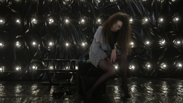 Glamour-looking model with afro hairstyle sitting on black cube. Fashion Video.