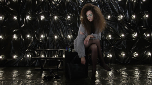 Glamour-looking model with afro hairstyle sitting on black cube. Fashion Video. Glamour-looking model with afro hairstyle sitting on black cube. Fashion Video. Slow Motion. 4K 30fps ProRes 4444 supermodel stock videos & royalty-free footage