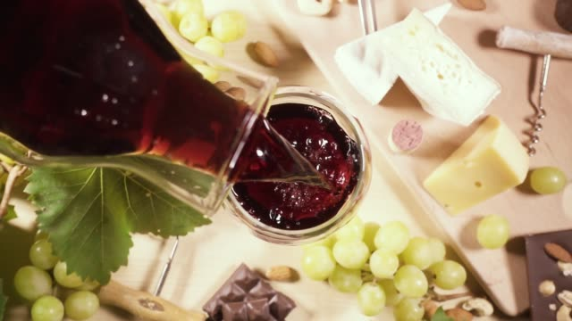 a glass and a bottle of wine and a snack top view - декантер стоковые видео и кадры b-roll
