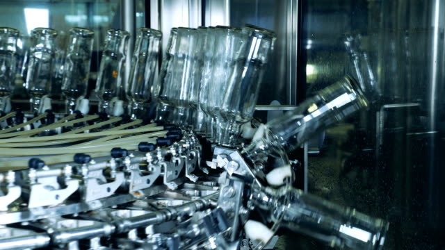 Glass bottles are getting transported by a round conveyor