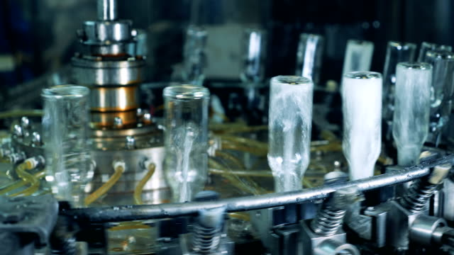 glass bottles are getting washed from inside while rotating along the conveyor - vodka video stock e b–roll