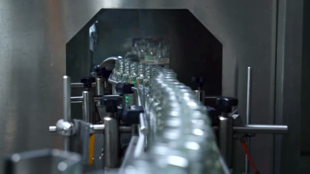 Glass bottles on the conveyor belt. Robotic automation line.