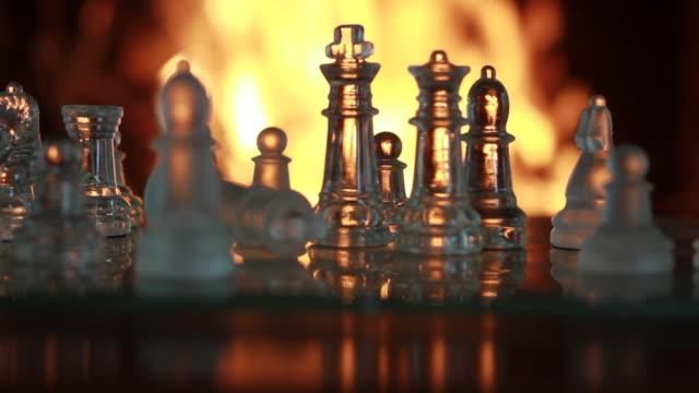 vídeos de stock e filmes b-roll de glass chess figures fade to fire - filosofia