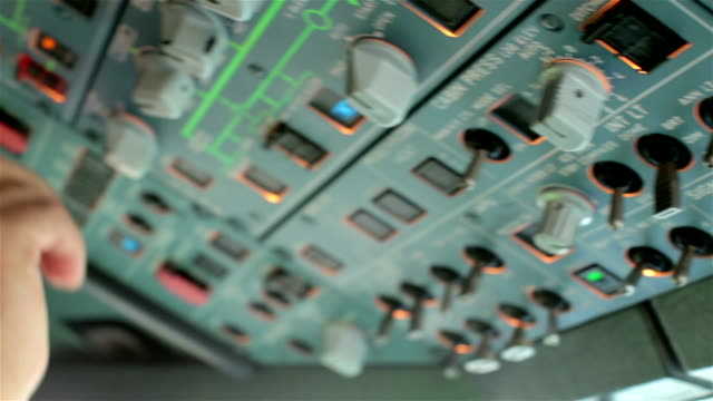 glass cockpit cabin. pilot hands operating on electronic deck panel, switch controls of aircraft, preparation for take off or landing on airbus a319 a320 - design for safety bildbanksvideor och videomaterial från bakom kulisserna