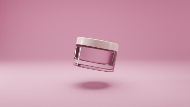 vaso vuoto cosmetico in vetro con coperchio bianco su uno sfondo rosa isolato. la bottiglia ruota lentamente nell'aria. cura della pelle cosmetica femminile. esempio di layout del prodotto di bellezza del pacchetto. animazione 3d realistica - mercanzia video stock e b–roll