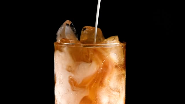 glass cup with ice and drink on black background. - coffee стоковые видео и кадры b-roll