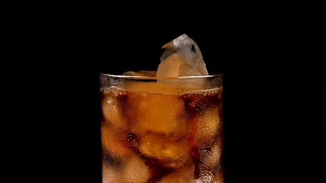vídeos de stock, filmes e b-roll de copo de vidro com gelo e bebida em fundo preto. - tea drinks
