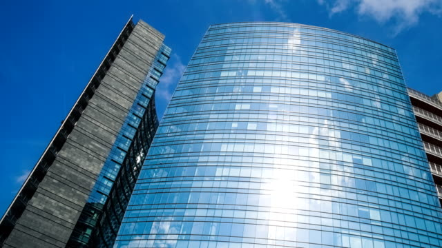 glass facade of a modern buildings and clouds - lombardia video stock e b–roll