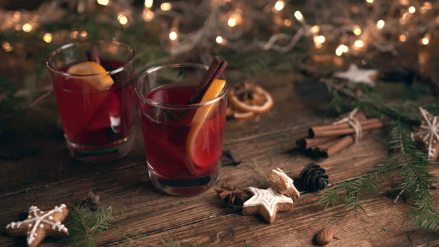 Glass filled with mulled wine with oranges and cinnamon, surrounded by fir branches and spices