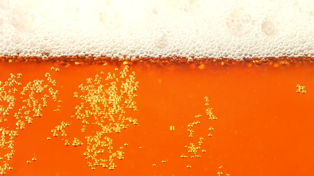 Glass full of beer moving bubbles. Slow motion. Closeup video