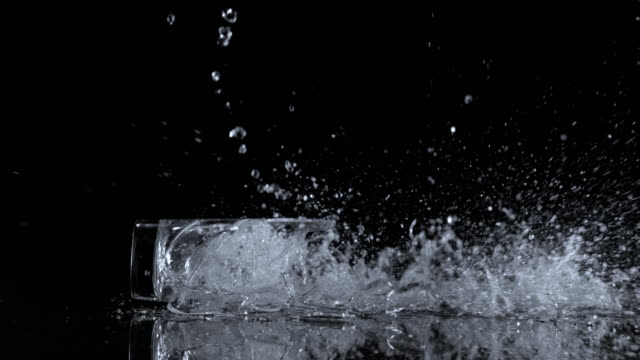 SLO MO LD Glass full of water hitting the surface and shattering