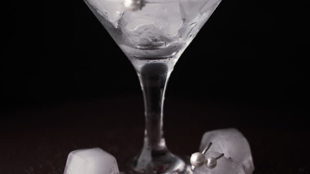Glass goblet with ice cubes and precious jewelry. Time lapse ice is melting.