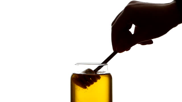 Glass jar of honey with wooden drizzler, pick it up, isolated on white, slow motion video